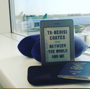 My travel companions: Between the World and Me on my Kindle, passport, and neck pillow